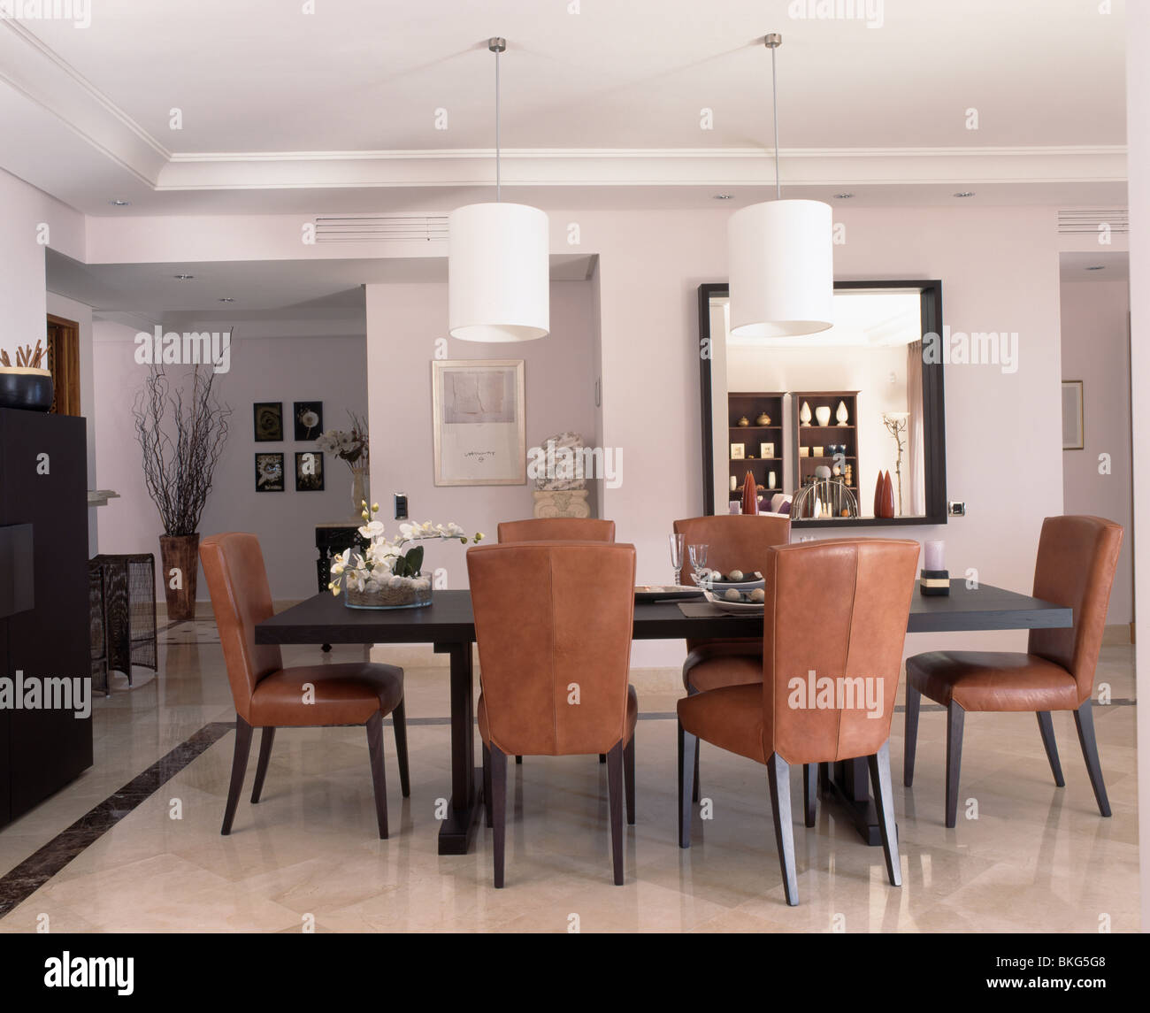 upholstered tan leather chairs at table in modern white dining room BKG5G8