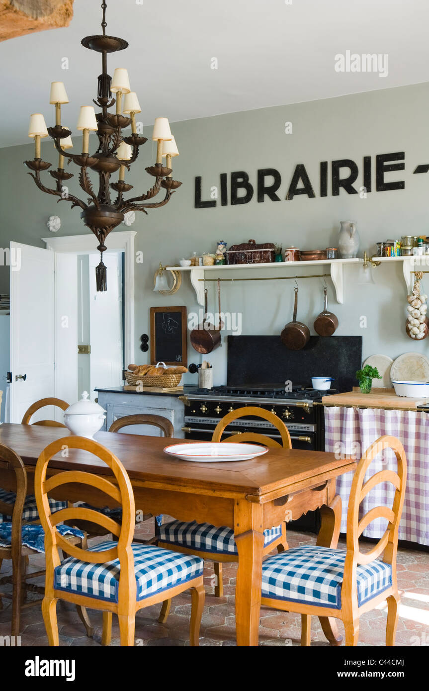eclectic kitchen with wooden dining table lamp chandelier and art C44CMJ