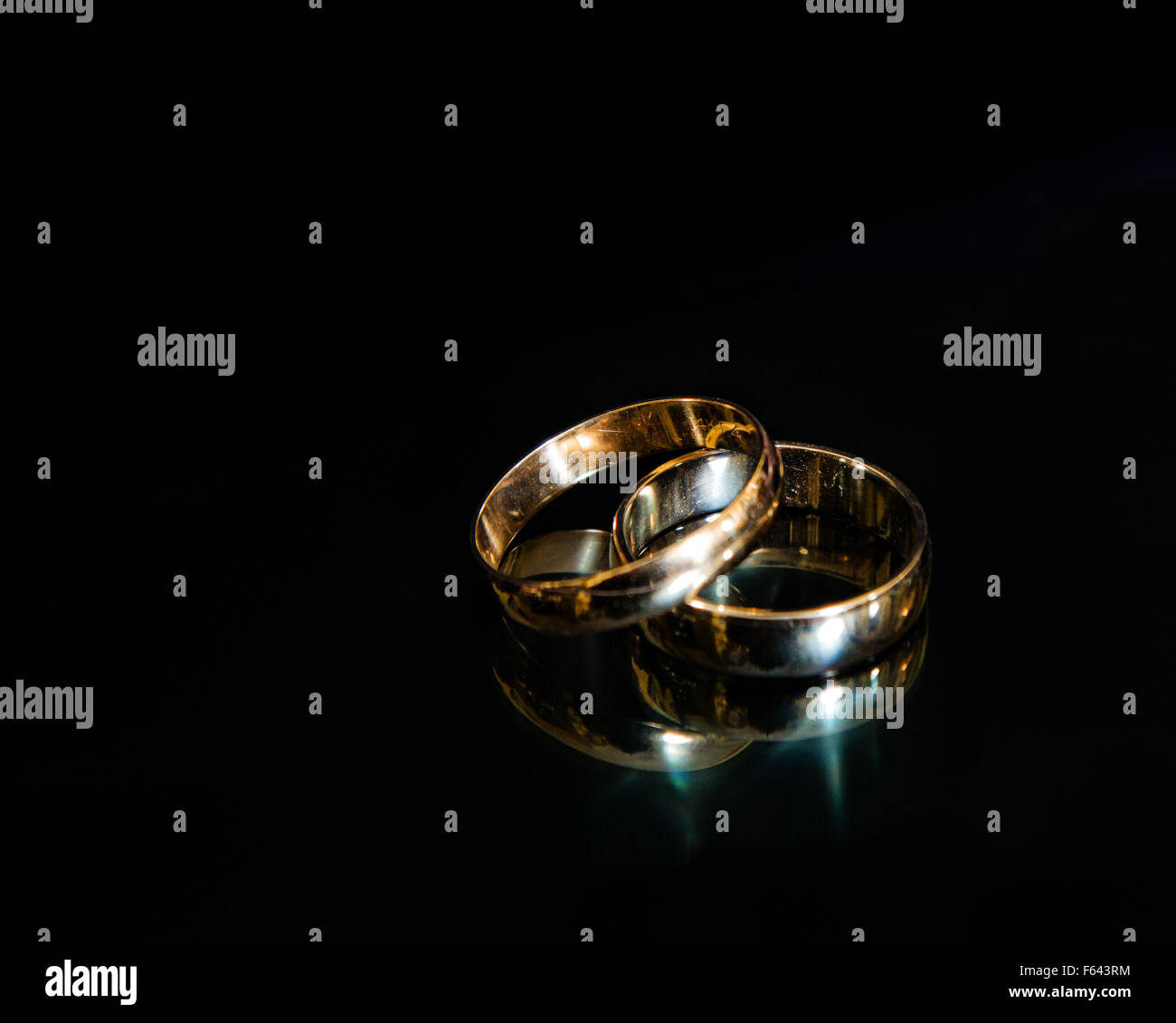 gay wedding rings gay mens wedding rings Two men s wedding bands on a reflective black background Stock Image