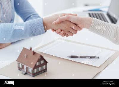 Real estate broker and customer shaking hands after signing a Stock Photo: 134200174 - Alamy
