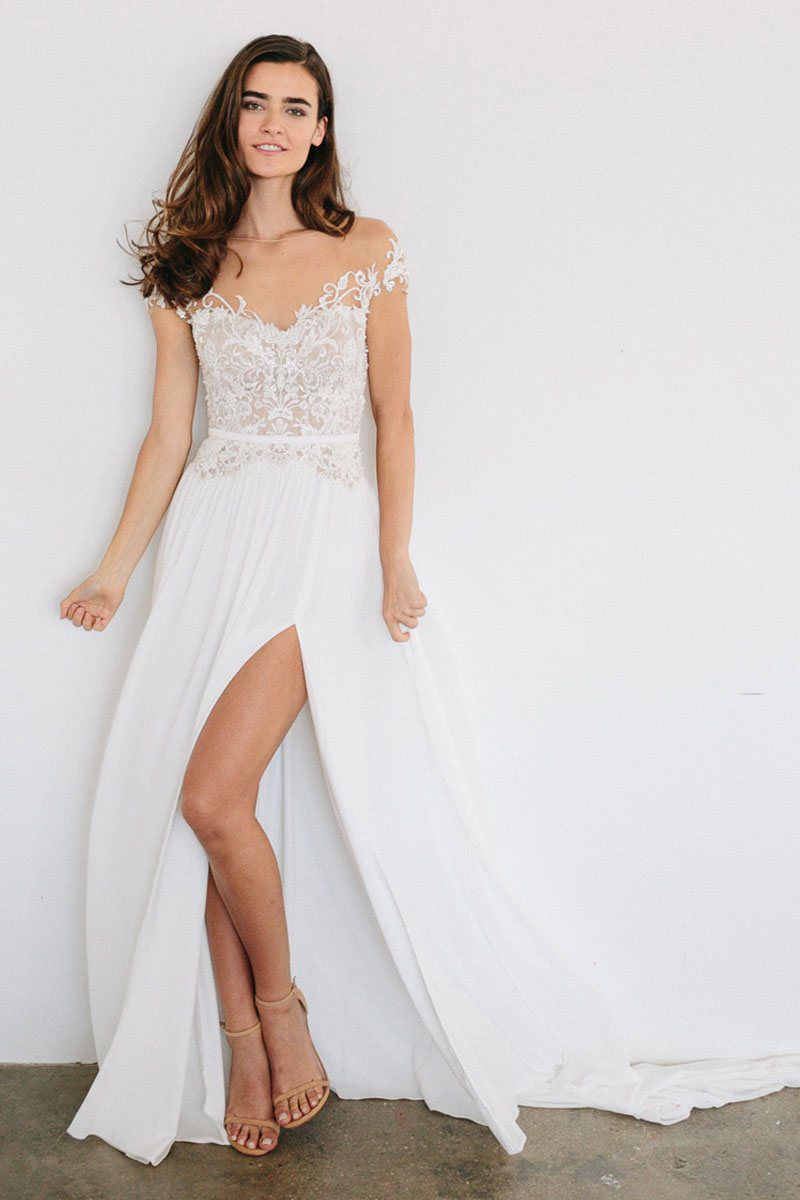 buy wedding dress online discounted wedding dresses A model wearing a white wedding gown with a lace top and full skirt with a
