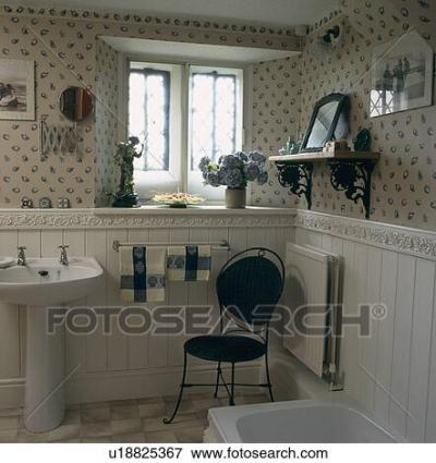 Picture of Blue and white wallpaper and metal chair in cottage bathroom with white raised tile ...