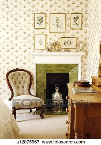 Picture of Button-back Victorian chair beside fireplace in bedroom with patterned wallpaper ...
