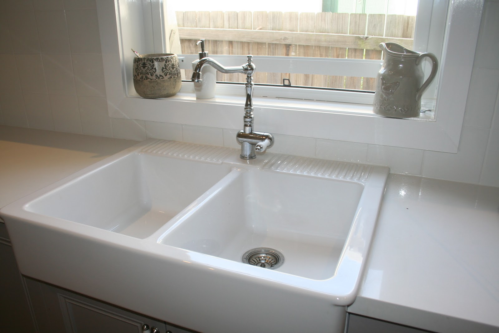 double farm sinks with single faucet in pure white kitchen countertop a window garden with two ceramic ornaments
