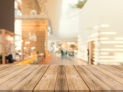 Wooden board empty table top on of blurred background. Perspective brown wood table over blur in ...