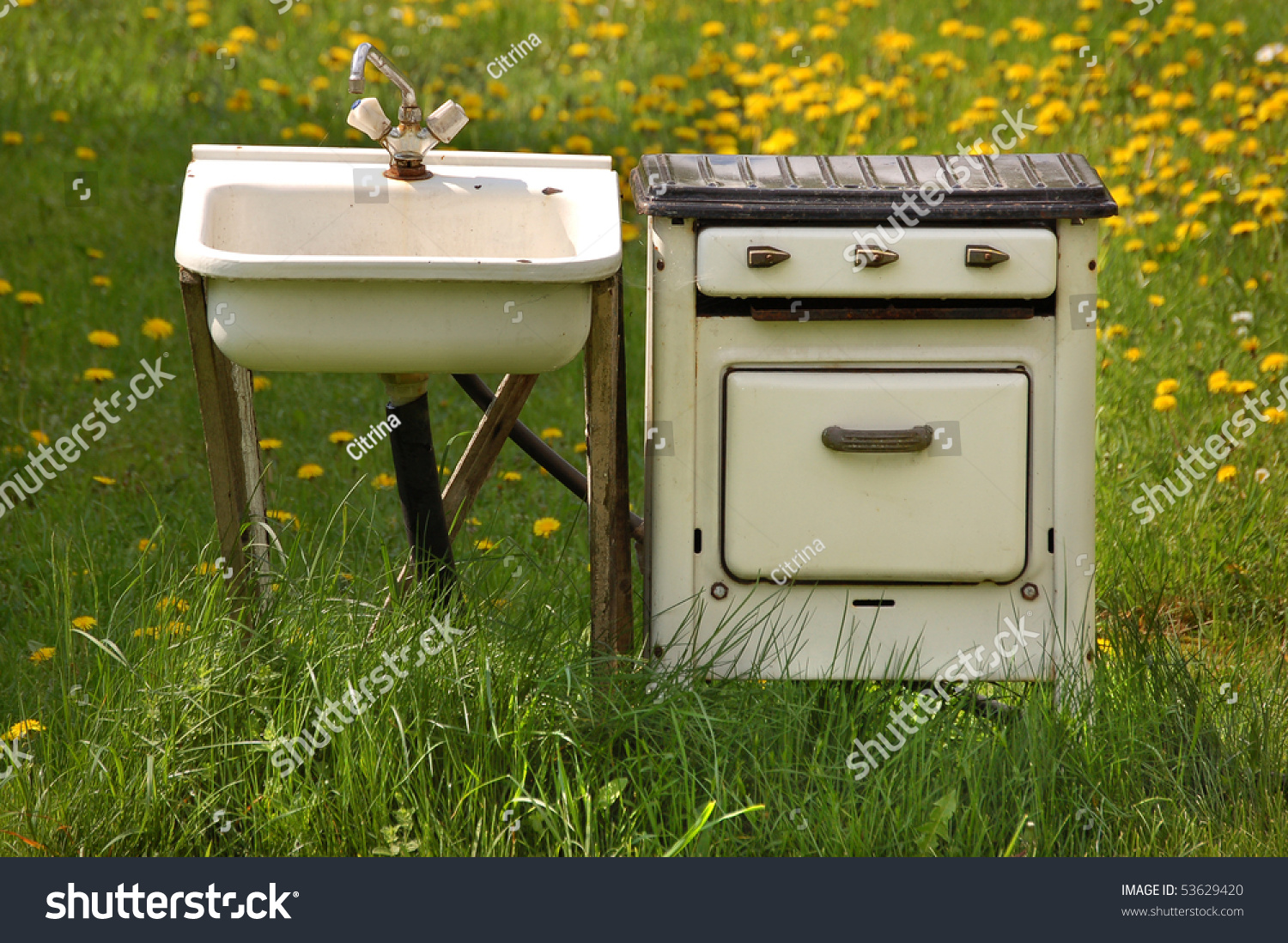 stock photo old run down kitchen sink with tap and pipes on a wooden stand and kitchen stove with three 53629420