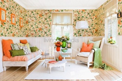 Lounge area with floral wallpaper above dado rail, white wall panelling below and orange and ...