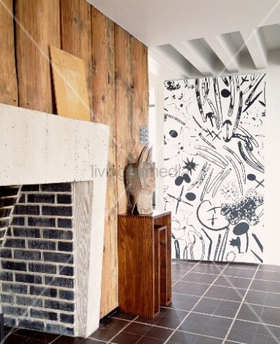 Brick fireplace on wood-clad wall opposite wall with black and white patterned wallpaper – Bild ...