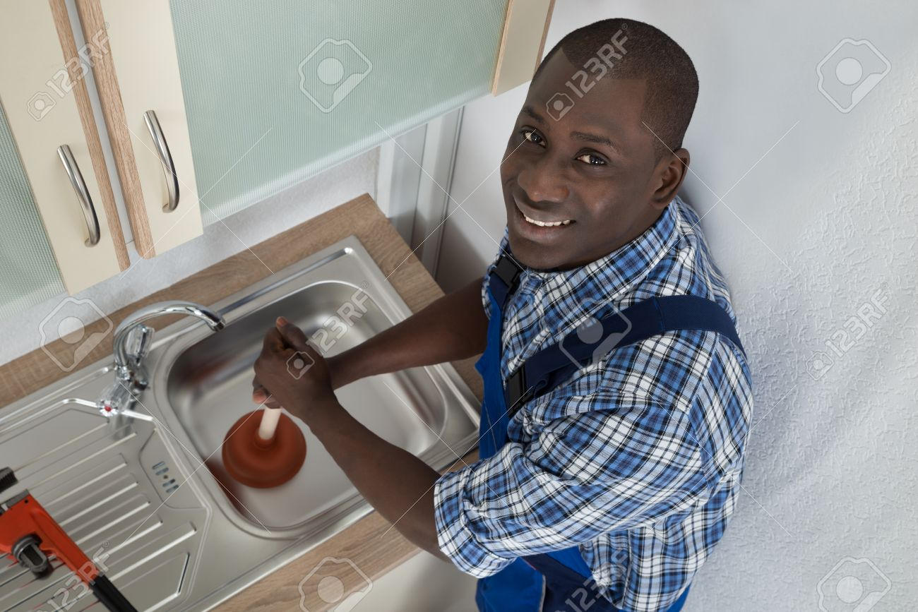 42193199 Young Happy African Plumber Using Plunger To Unclog Kitchen Sink Stock Photo