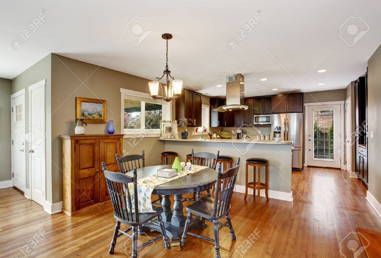 30056897 Dark brown kitchen room with round rustic dining table with chairs Stock Photo