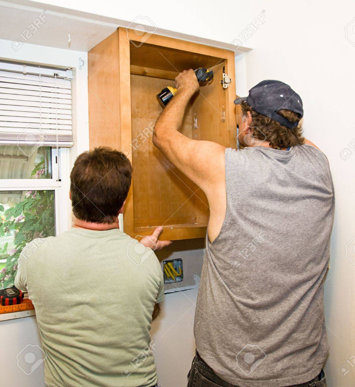 3766948 Carpenter and helper installing kitchen cabinets together  Stock Photo