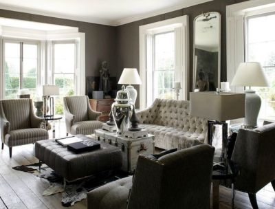 This elegant and refined living room was designed with grey taupe wallpaper, bay windows, and ...