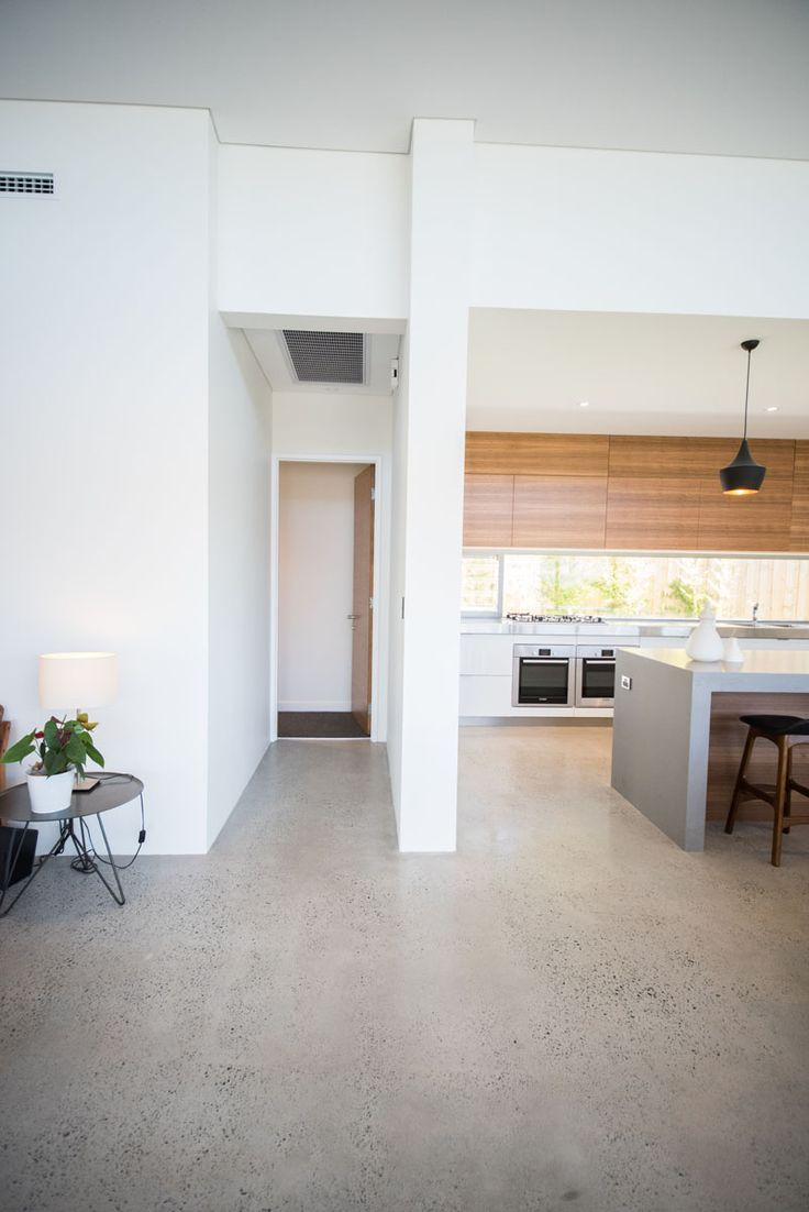 polished concrete flooring concrete floor kitchen Red Tail Homes Sleek Concrete Kitchen White and timber look cabinetry with glass splash back and black pendant lights makes for a beautiful modern kitchen