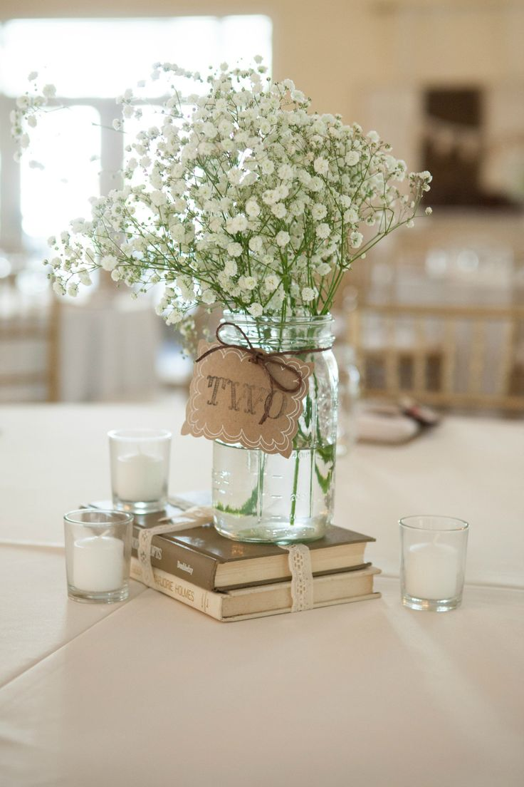 mason jar weddings rustic wedding centerpieces Simple rustic centerpiece using old books mason jar vases Baby s Breath and