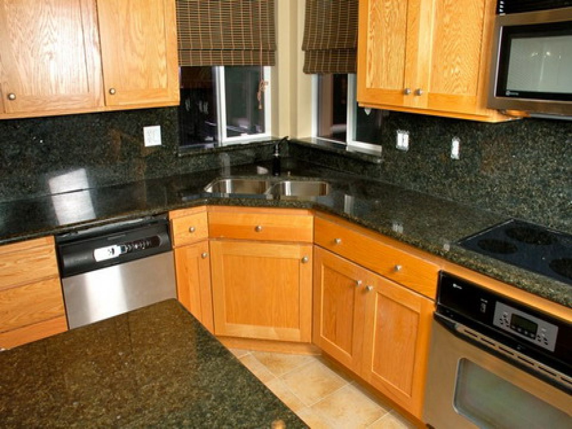 kitchen sink kitchen cabinets Fashionable Corner Kitchen Sink With Unstained Oak Kitchen Cabinet With Dark Granite Countertop As Well As Grey Wall Tiles Backsplash And Chrome Modern