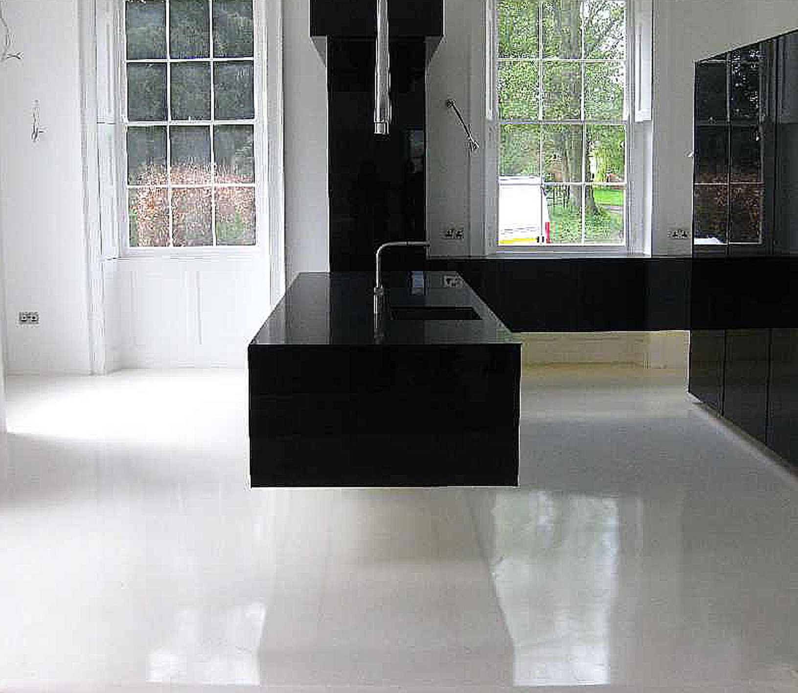 epoxy flooring kitchen Ultra modern gloss black floating cantilevered kitchen with pure white seamless resin floor