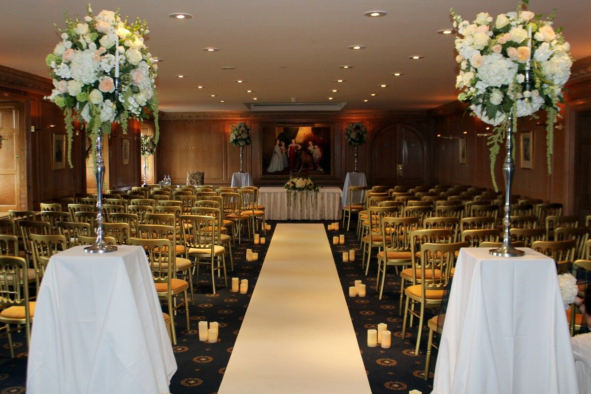 wedding aisle runner White carpet aisle runner and LED Candles decorating the wedding ceremony room at Brocket Hall