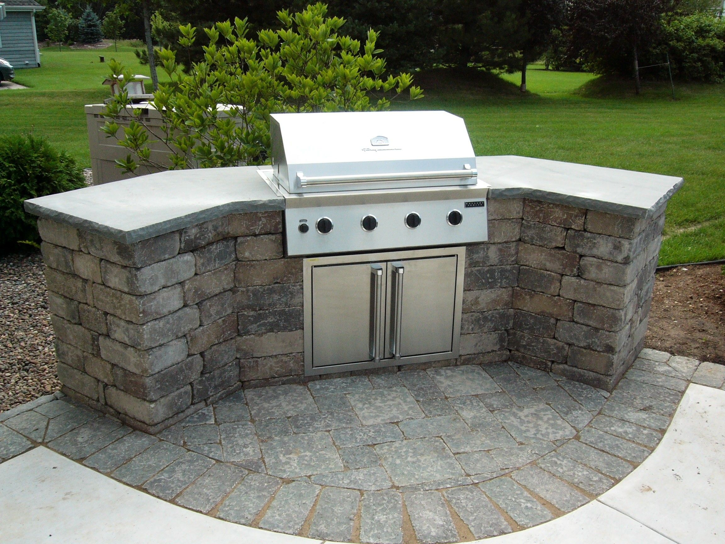 kitchen countertop materials Curved Stone Prefab Kitchen Island With Gray Concrete Countertop And Barbeque Grill On Backyard Garden