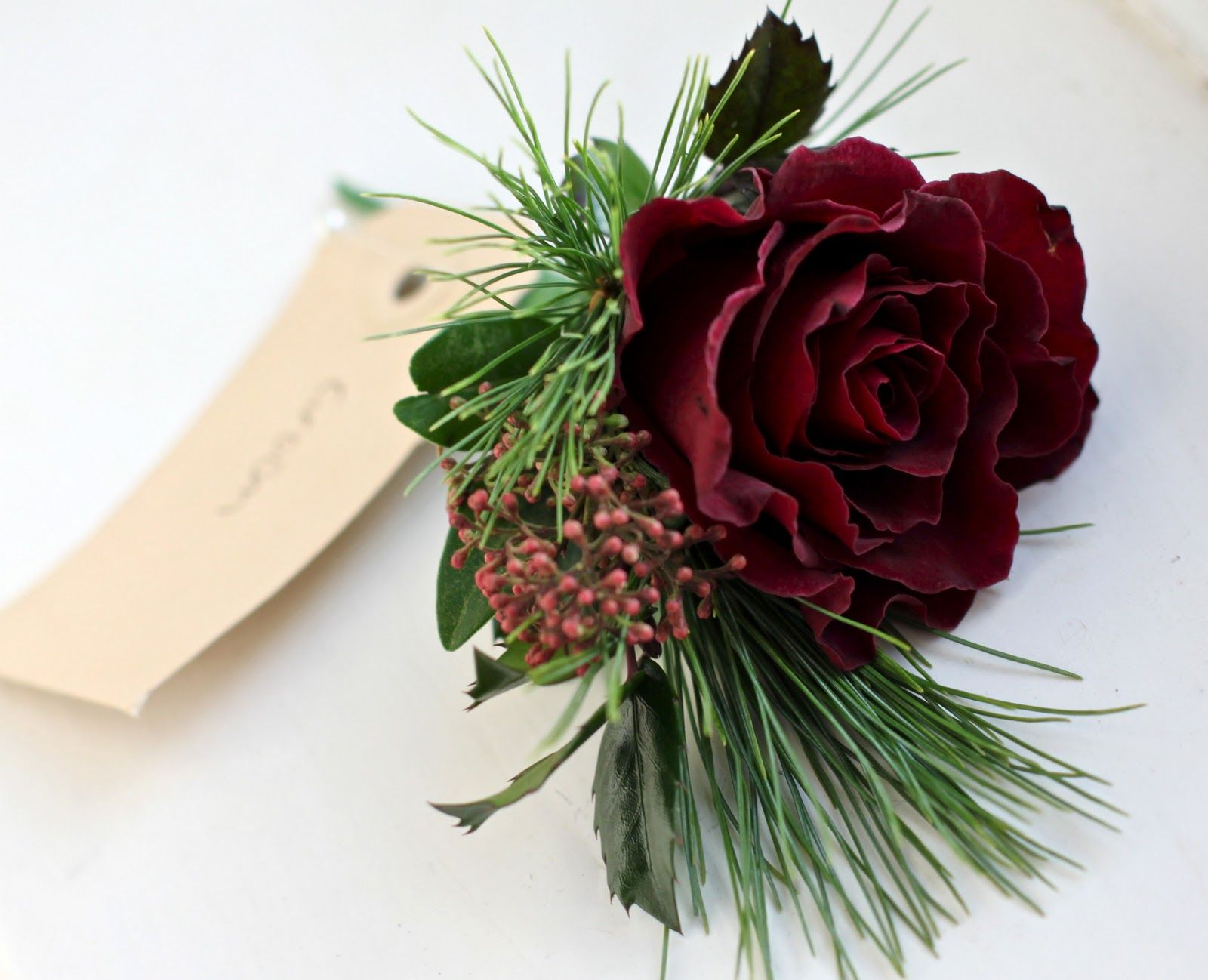 winter wedding flowers flowers for weddings burgandy wedding snowflake theme Winter buttonhole of burgundy rose pine holly and skimmia for the