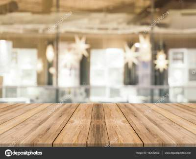 Wooden board empty table top on of blurred background. Perspective brown wood table over blur in ...