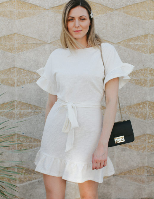 Cute summer ruffle dress styled by top US fashion blog, Tea Cups & Tulips: image of a woman wearing an H&M cream ruffle dress, Furla crossbody bag, H&M mules, ASOS hat and Amazon pearl hair clip.
