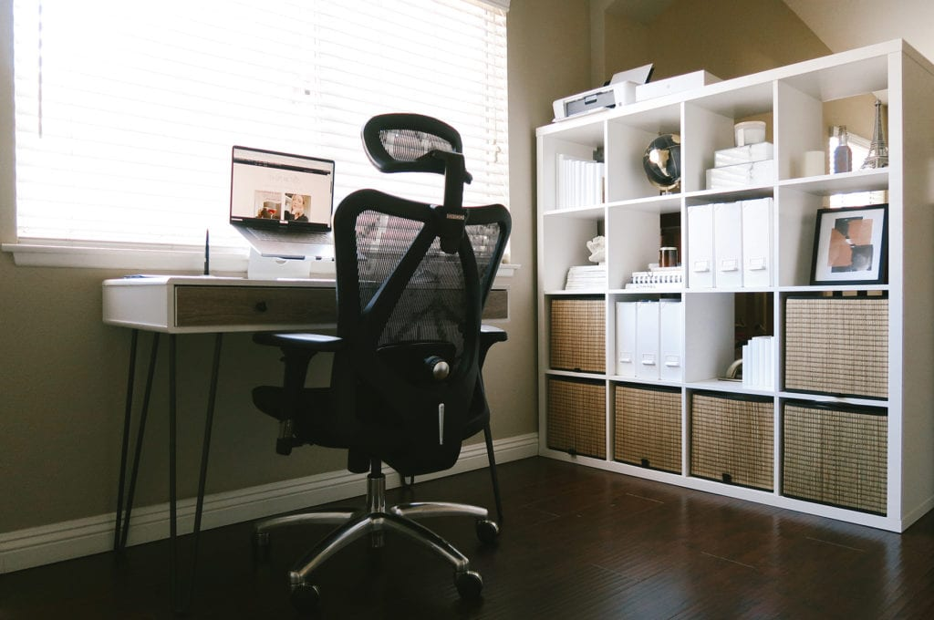 Work From Home Essentials To Boost Your Productivity |Work from home office essentials | Work From Home Office essentials by popular LA lifestyle blog, Tea Cups and Tulips: image of a home office with a Mac laptop, white desk, white storage shelving with woven cube bins, blue light glasses, and black rolling chair.