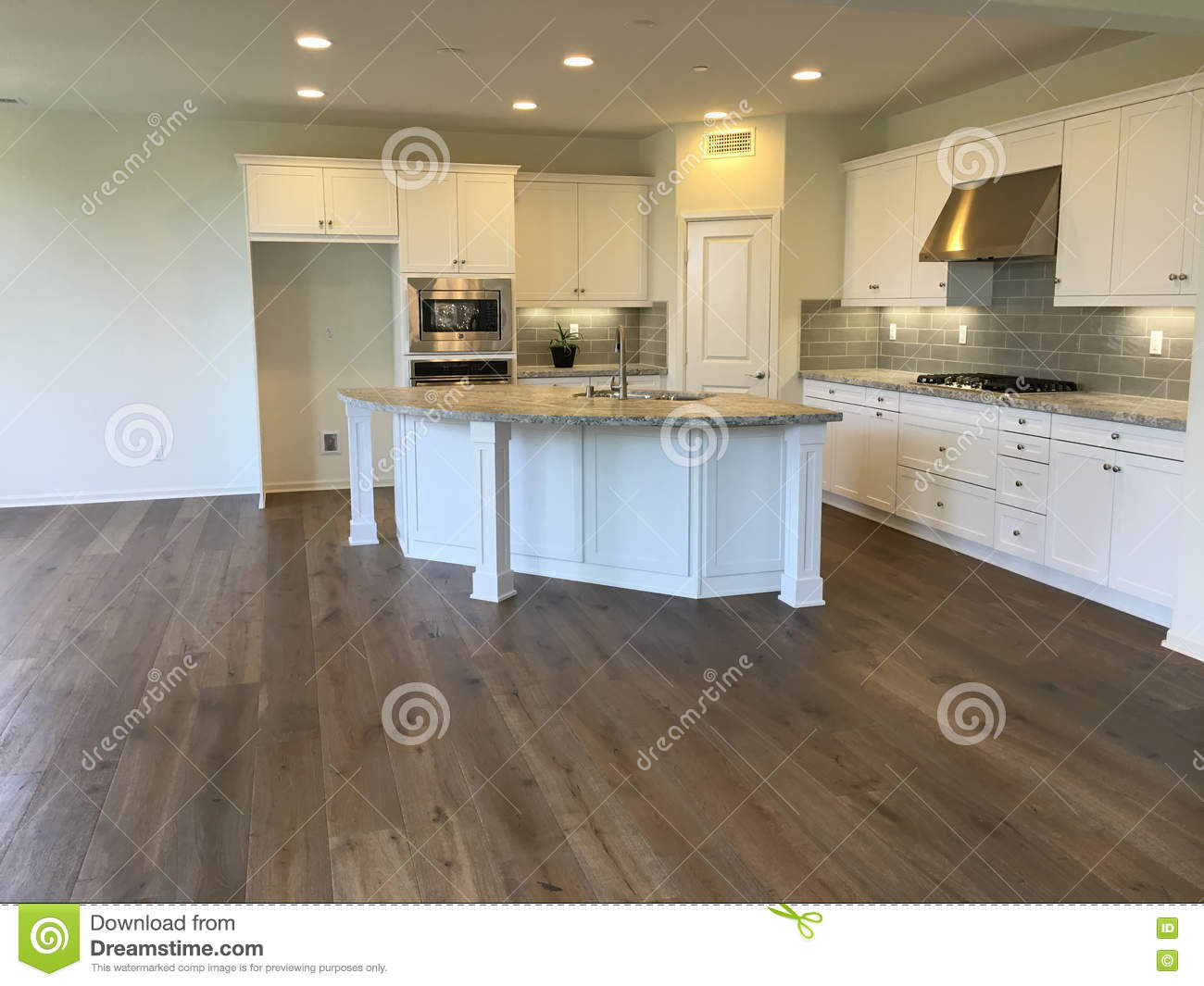 empty beautiful modern white kitchen wood floors stainless steel appliances granite counters sink middle island 70635706