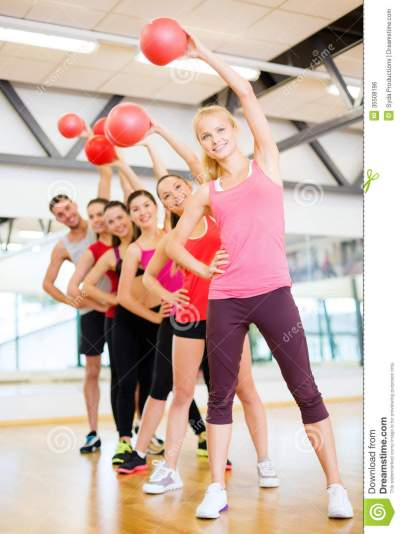 Group Of Smiling People Working Out With Ball Stock Photo ...