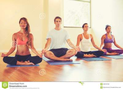 People Relaxing And Meditating In Yoga Class. Stock Photo ...