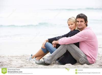 Young Couple On Holiday Sitting On Winter Beach Royalty-Free Stock Photography | CartoonDealer ...