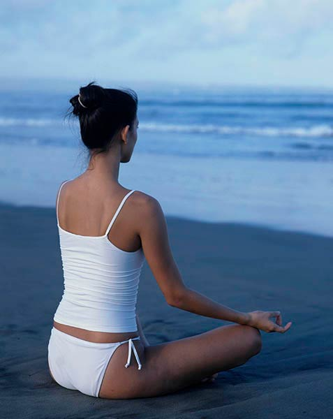 Brunette Model Meditating on the Beach