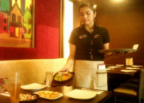 Salah seorang karyawan Pizza Hut saat menyajikan hidangan. Foto AFRIZAL