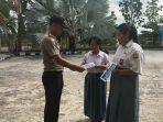 Salah satu personil Polsek Gunung Kijang saat memberikan brosur penerimaan POLRI tahun 2020