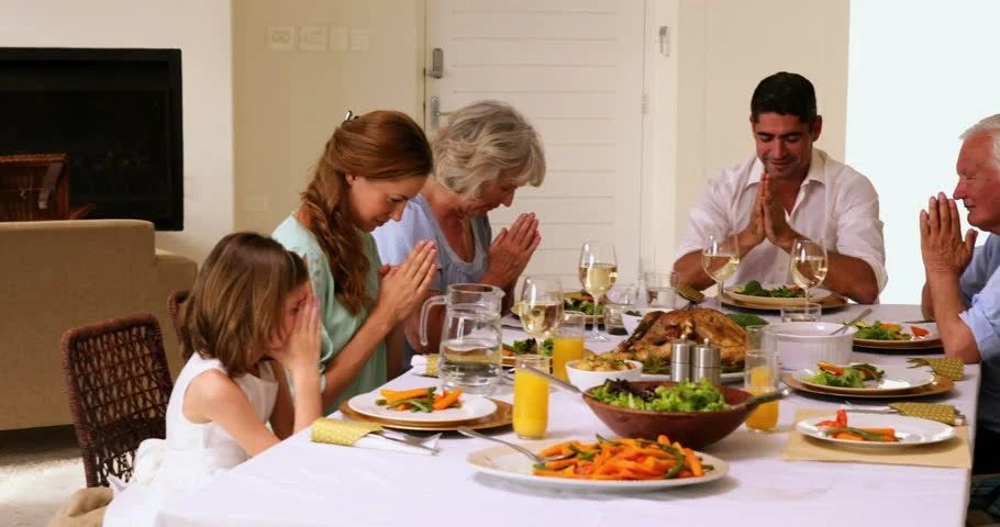 Extended Family Praying Before Dinner At Home In The ...