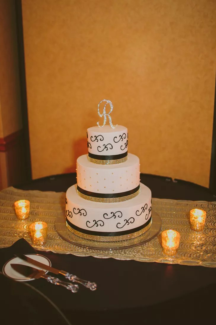 Tiered White Wedding Cake with Black and Gold Ribbon and Monogram