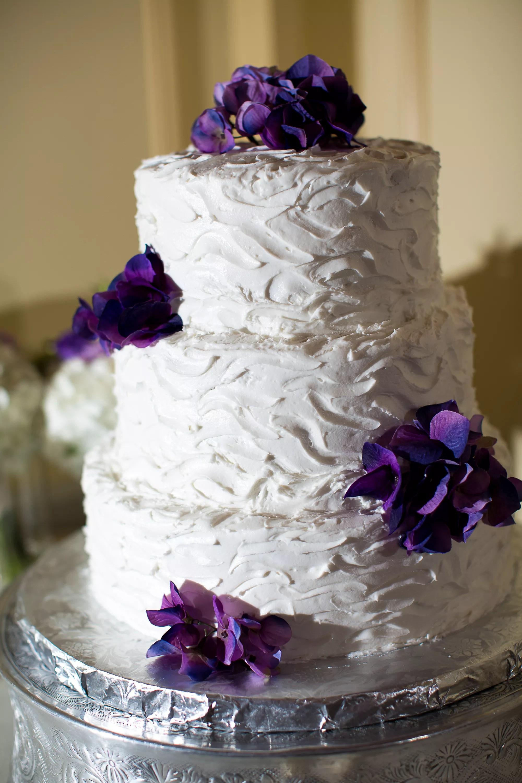 Three Tier Buttercream Wedding Cake With Purple Flowers