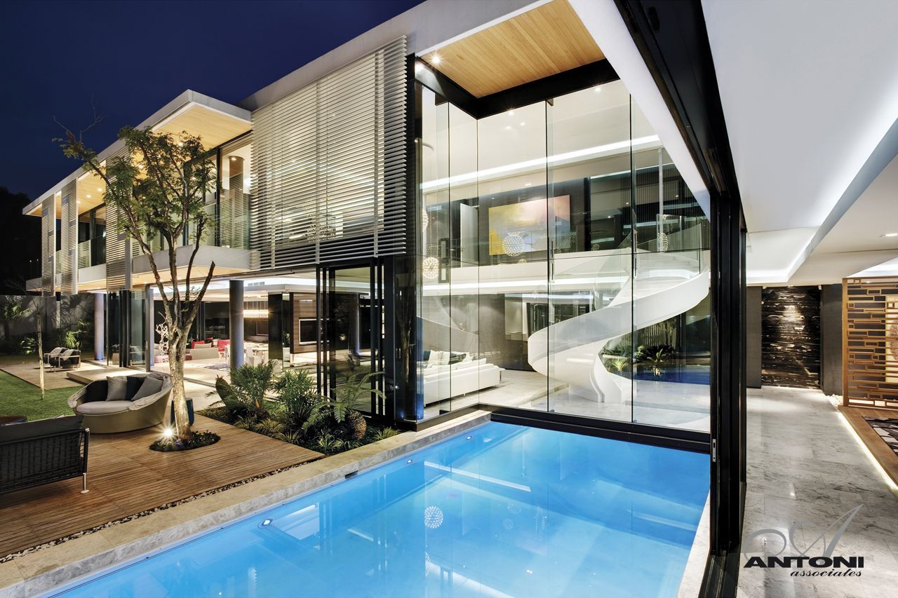 Modern Mansion With Perfect Interiors by SAOTA   Architecture Beast Swimming pool and glass wall as part of facade at night