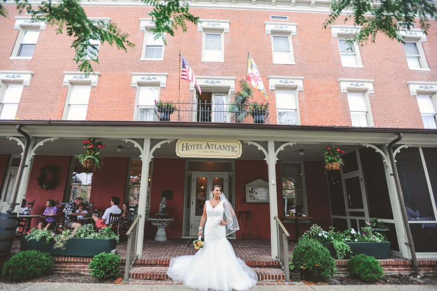Weddings Main   The Atlantic Hotel   Historic Berlin MD Bustle Bride standing on the steps to the front entrance of Atlantic Hotel  Berlin MD