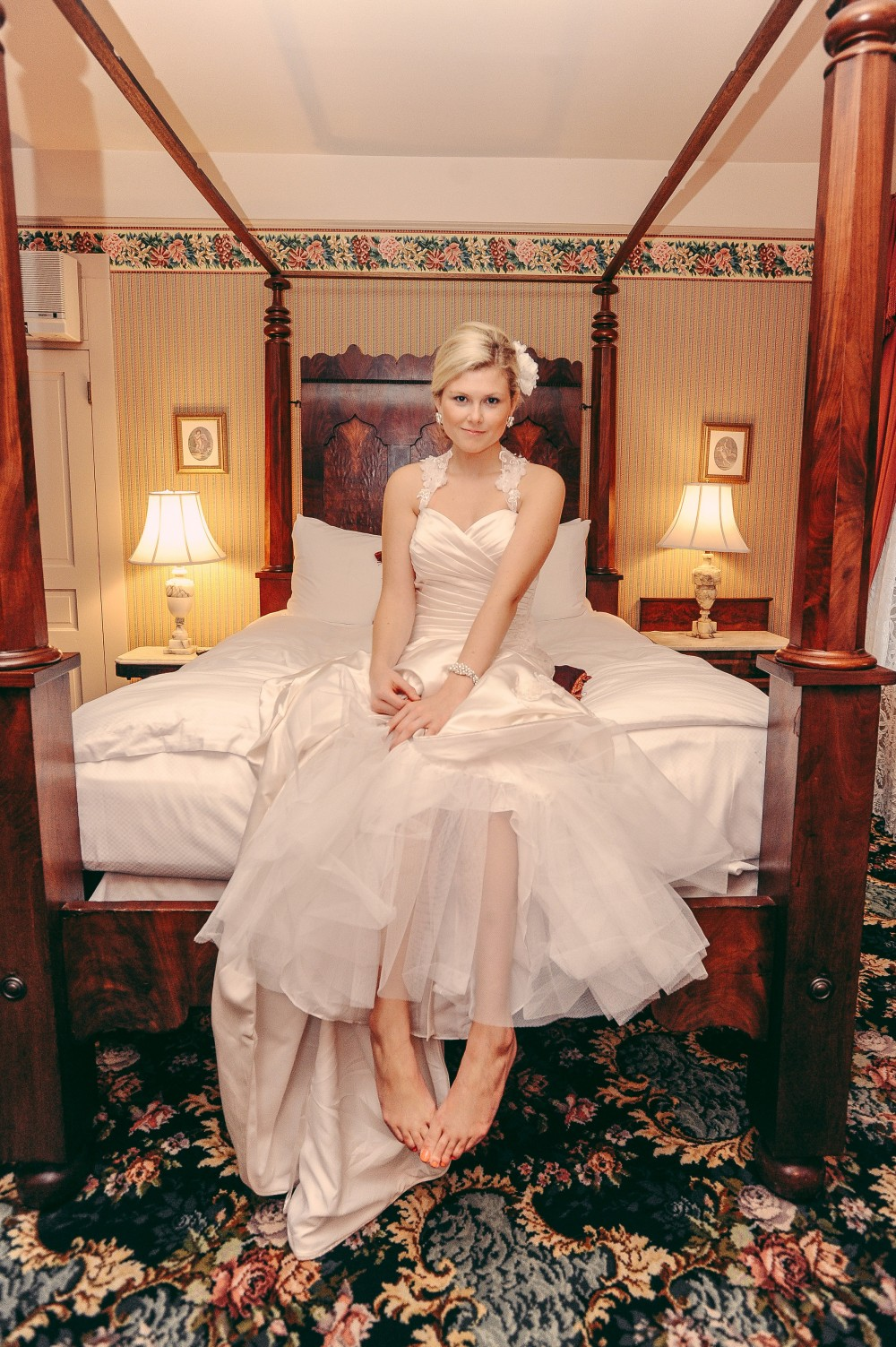 Weddings Main   The Atlantic Hotel   Historic Berlin MD Bride sitting on bed in Atlantic hotel in silk dress with no shoes
