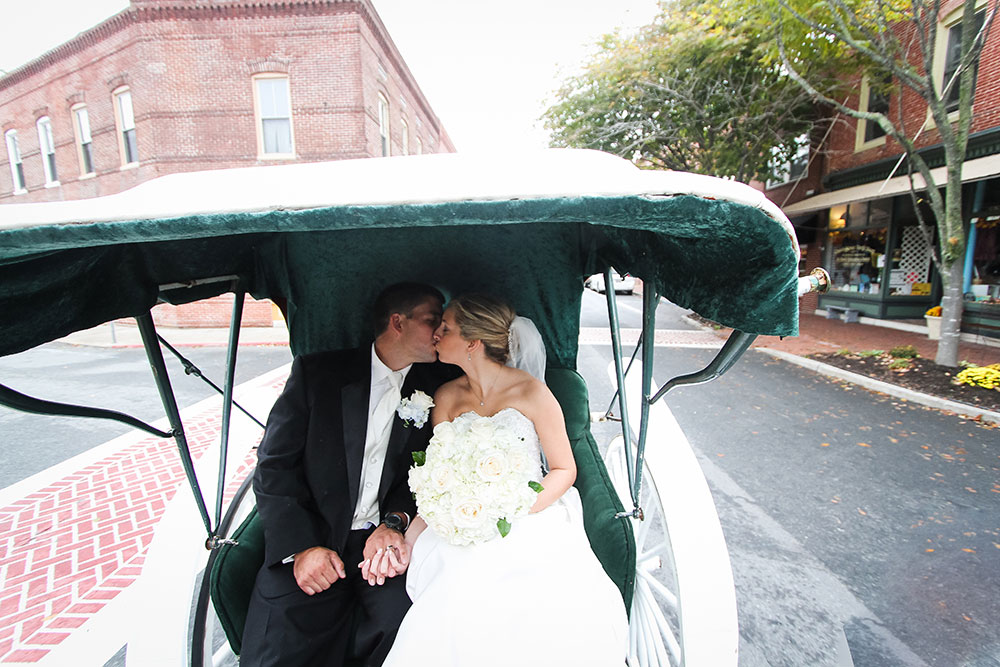 Weddings Main   The Atlantic Hotel   Historic Berlin MD Newlyweds kissing in a carraige after their wedding ceremony in Berlin MD