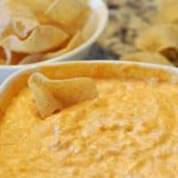 buffalo chicken cheese dip in white bowl with tostido chip