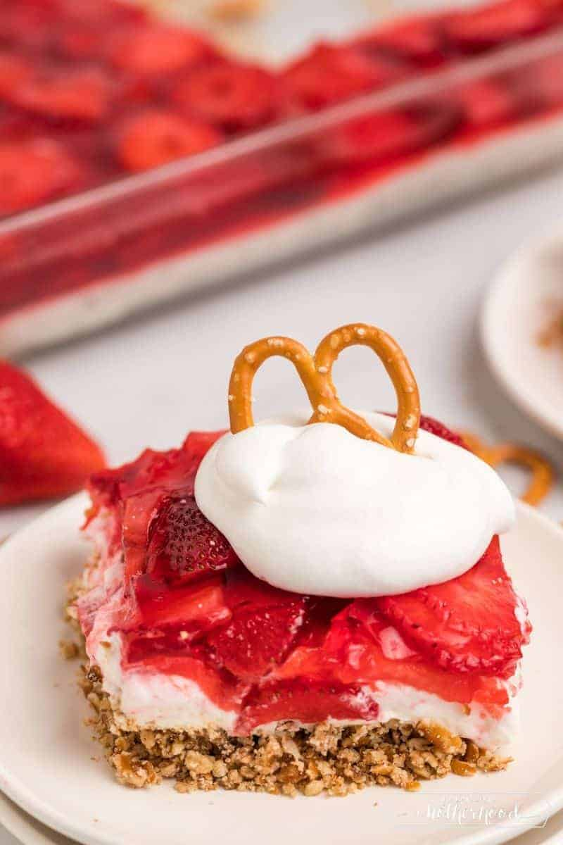 Slice of strawberry pretzel salad with whipped cream and a pretzel on top.