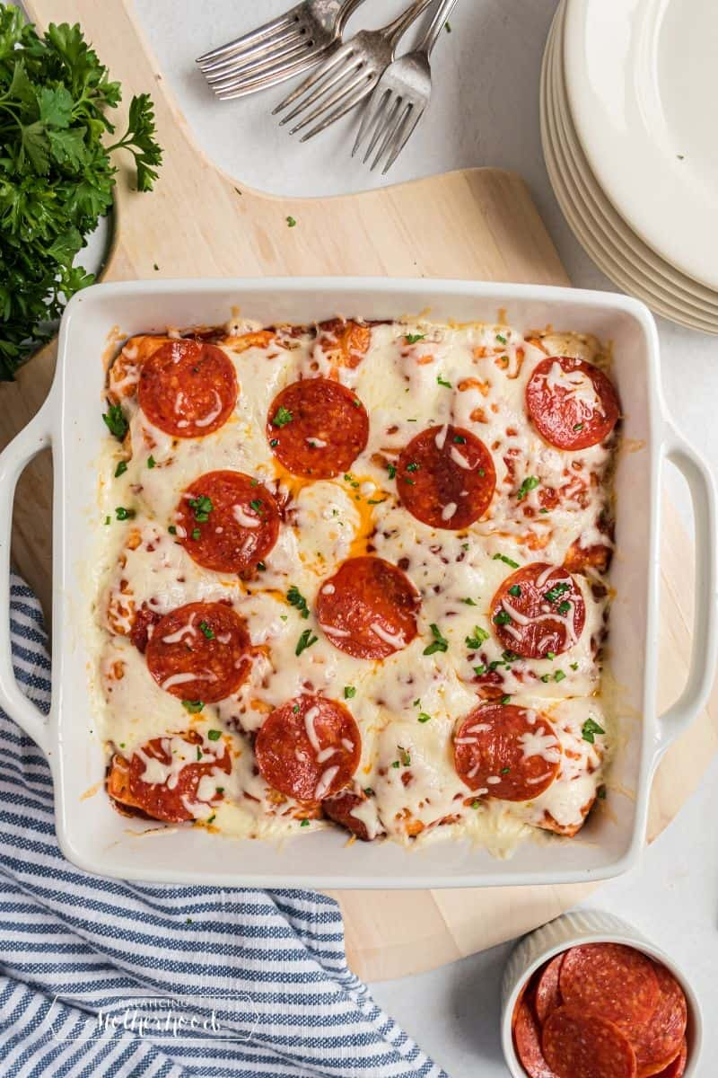 White casserole dish with bubble pizza fresh out of the oven.