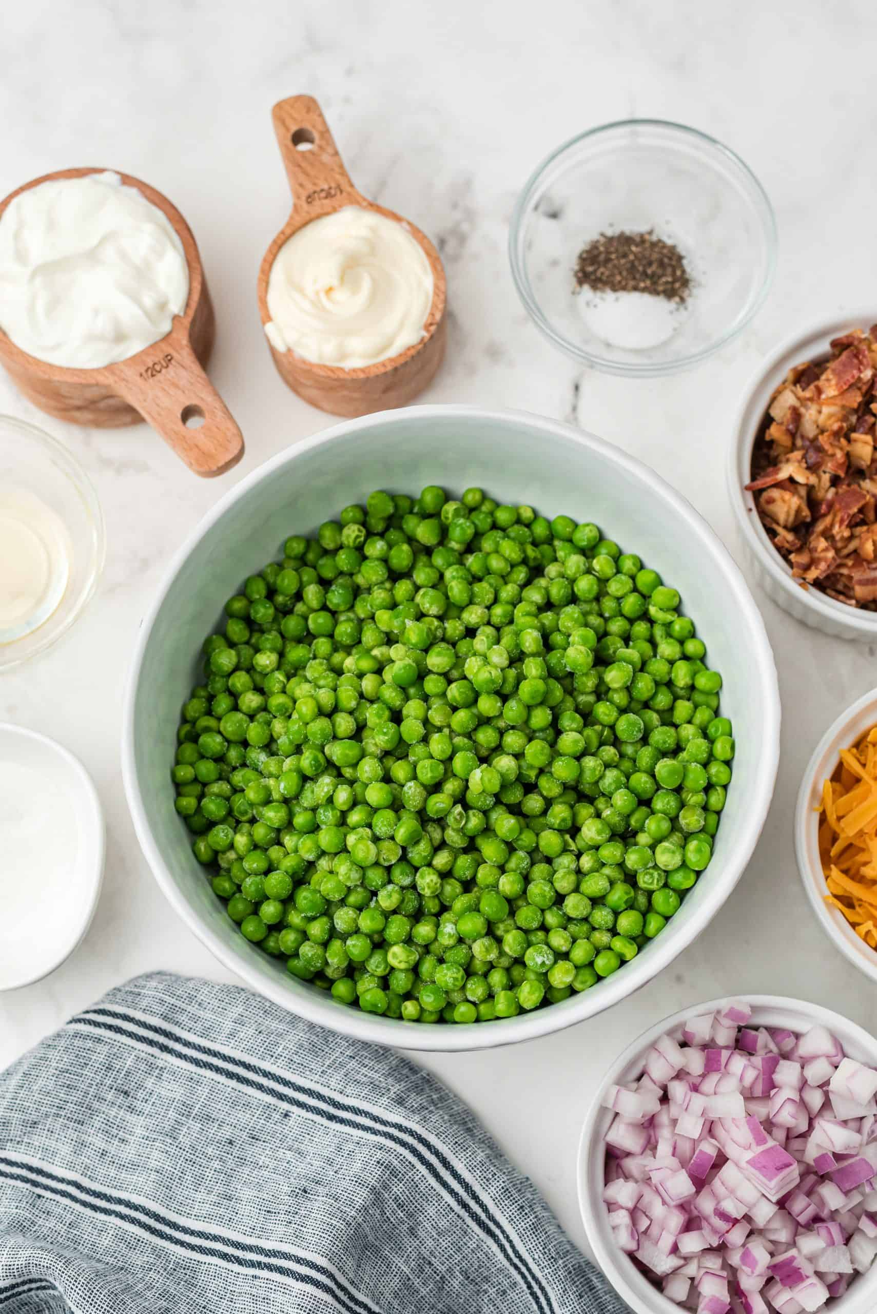ingredients: frozen peas, red onion, sour cream, mayonnaise, sugar, apple cider vinegar, salt and pepper