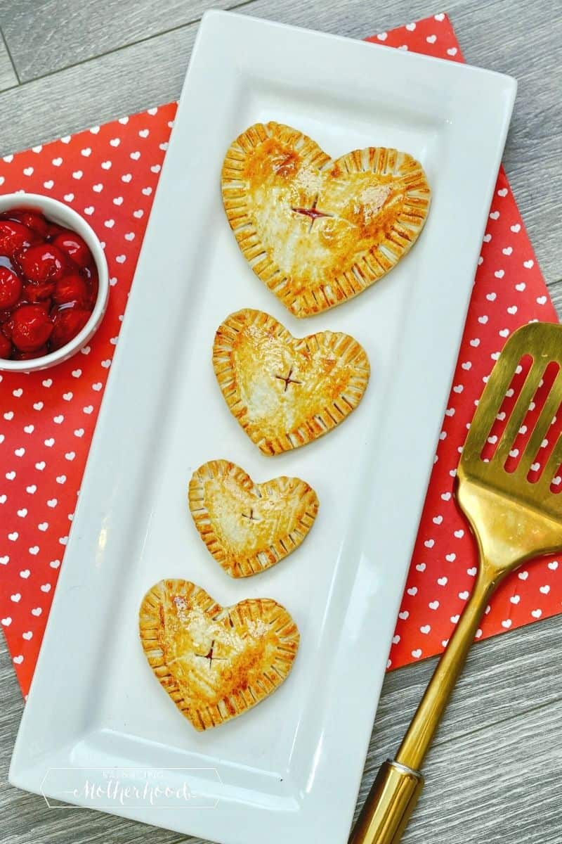 narrow white plate with four heart-shaped hand pies