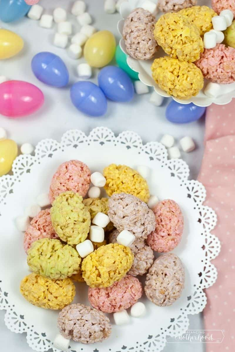 crispy treat eggs, yellow, pine and light purple on white tray surrounded by Easter eggs and mini-marshmallows
