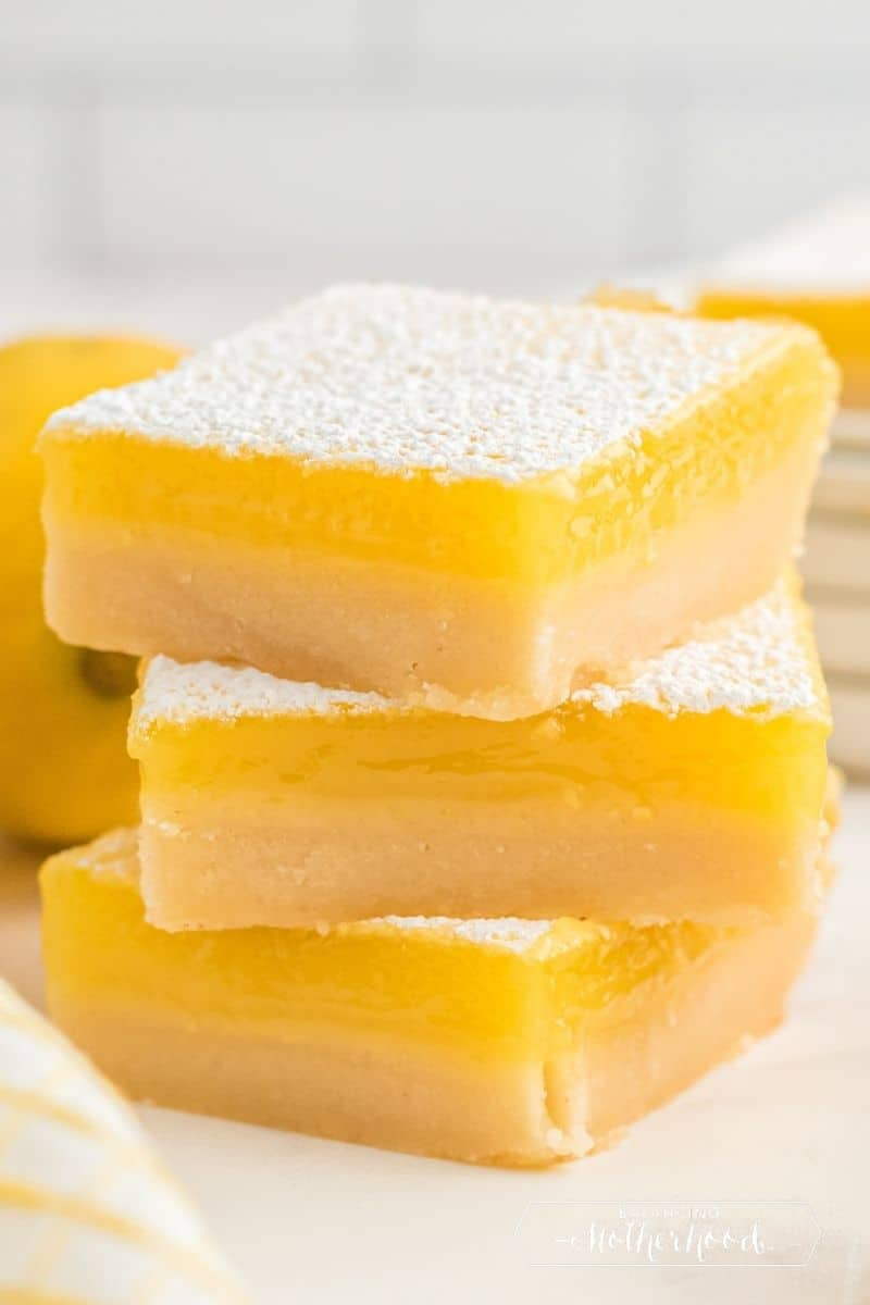 three square lemon bars stacked on top of each other