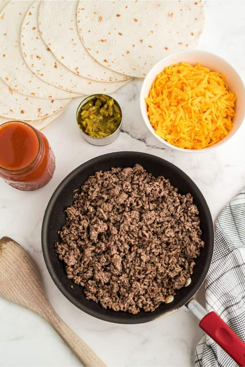 ingredients: ground beef, cheese, chiles, enchilada sauce, with tortillas spread out on counter