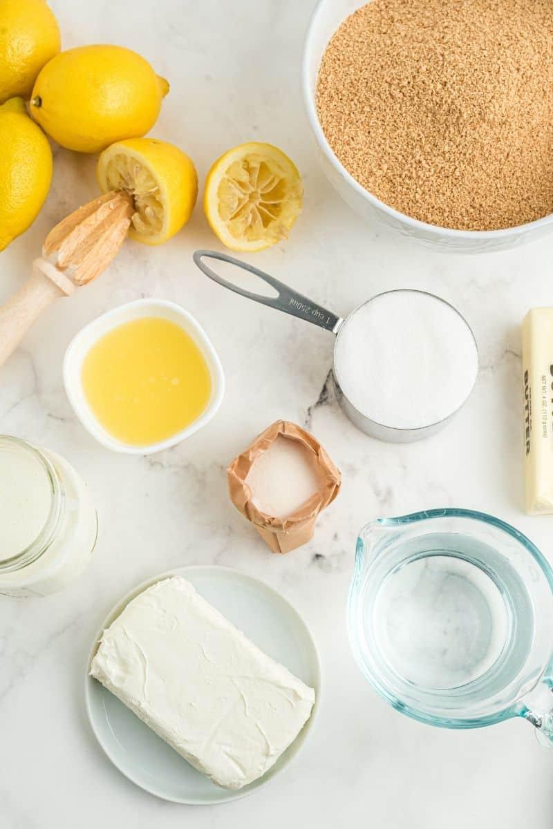 lemons cut in half, graham cracker crumbs, sugar, butter, water, gelatin, cream cheese, and cream in mason jar