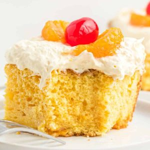 slice of golden cake with white frosting and oranges and a cherry on top